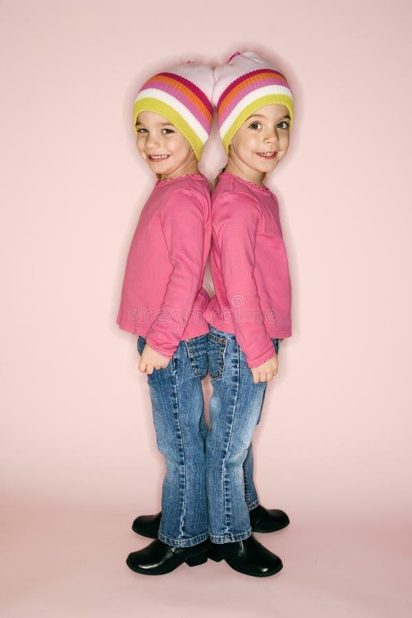 Jumeaux de jeune fille restant de nouveau au dos. photos stock