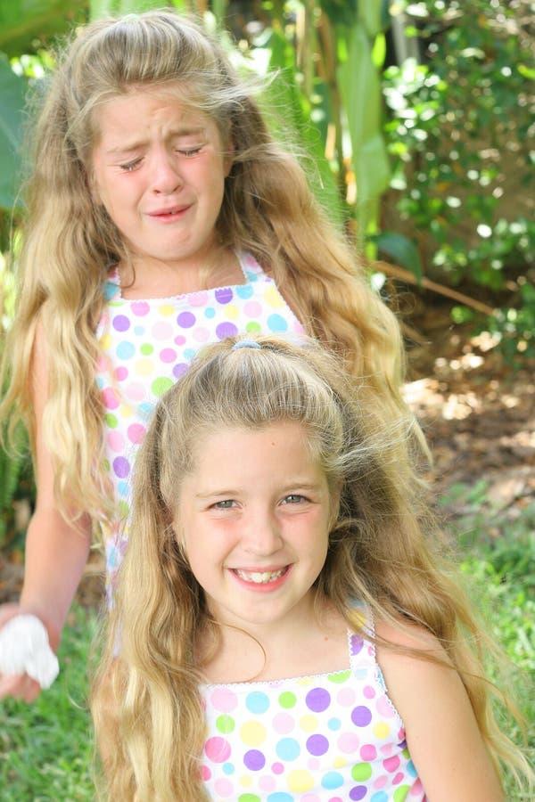 Jumeaux heureux et tristes image stock
