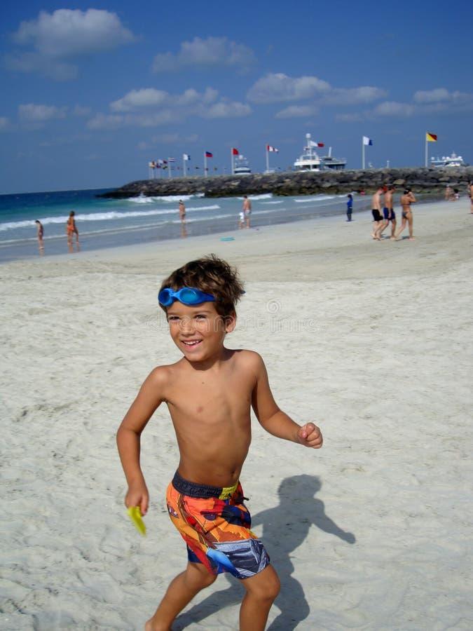 Happy boy on Jumeirah Beach in Dubai royalty free stock image