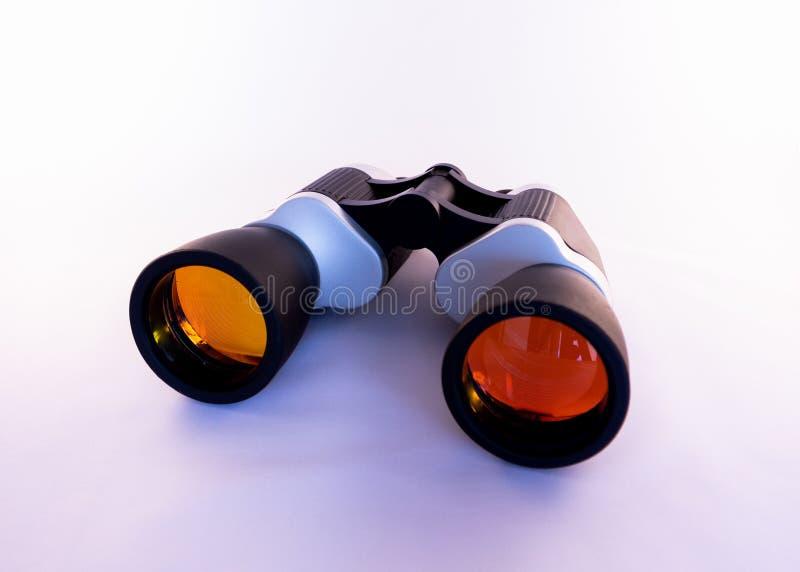 Jumelles avec les lentilles oranges colorées sur un fond blanc photographie stock libre de droits