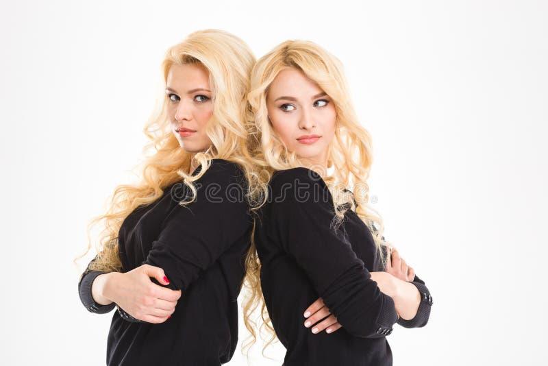 Jumelles sérieuses de soeurs avec des bras pliés image stock