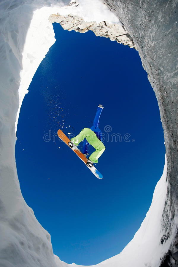 In jump. Below view of extreme snowboarder surrounded by rocky mounts covered with snow stock photos