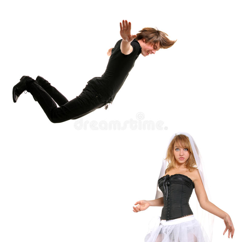 Jump. Young bride and flying groom funny portrait royalty free stock photography