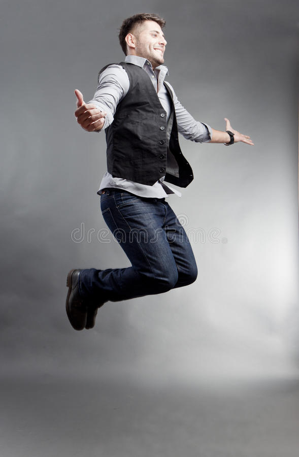 Jump. Young man dressed in jeans outfit jumping for joy stock photo