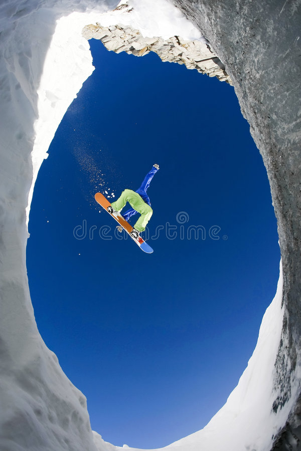 In jump. Below view of extreme snowboarder surrounded by rocky mounts covered with snow royalty free stock images