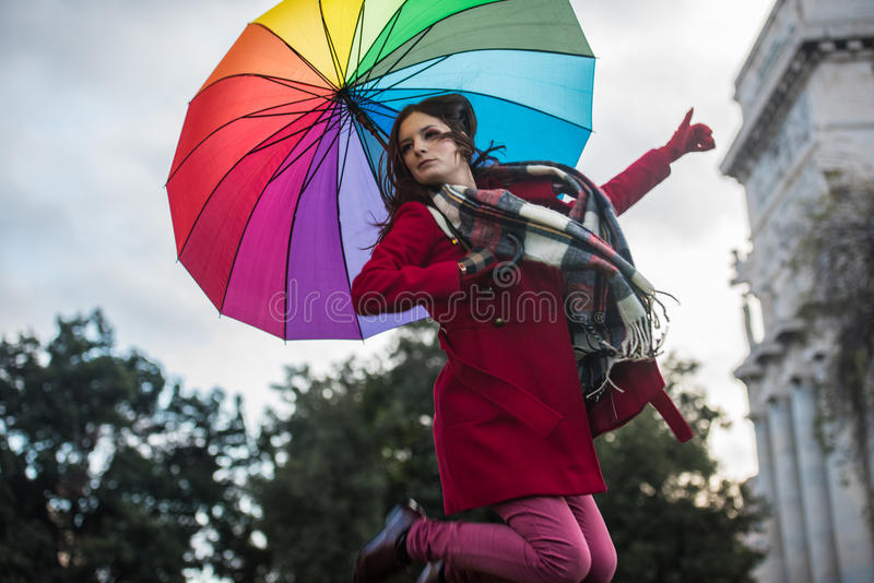 Jump in the air. Beautiful portrait of a stunning and gorgeous redhead french girl with small freckles and long hair jumping in the air with her colorful royalty free stock photography
