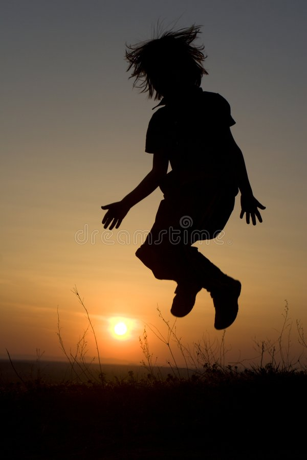 Jump Of Child In The Sunset Royalty Free Stock Image