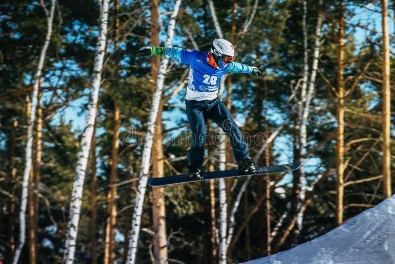 Jump and flight athlete snowboarder. Miass, Russia - February 20, 2016: jump and flight athlete snowboarder during Snowboard World Cup - Snowboard Cross stock photo