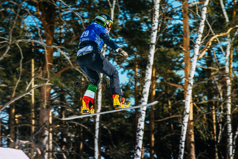 Jump and flight man athlete snowboarder. Miass, Russia - February 20, 2016: jump and flight man athlete snowboarder during Snowboard World Cup - Snowboard Cross royalty free stock image