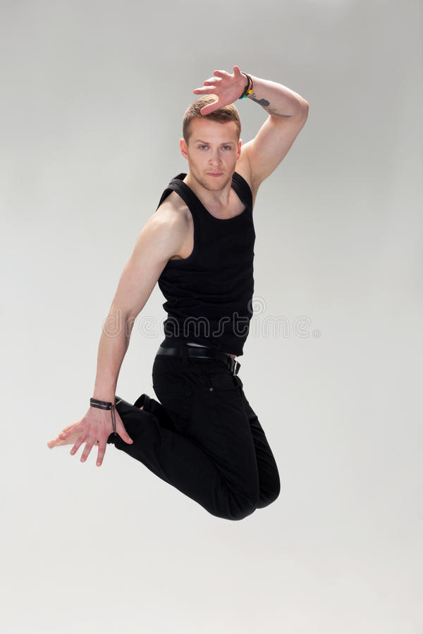 Jump. Handsome jumping guy in black clothes stock image