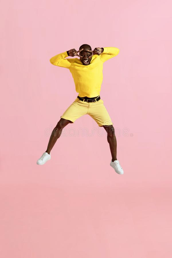 Jump. Happy man jumping in air, screaming on pink background stock images
