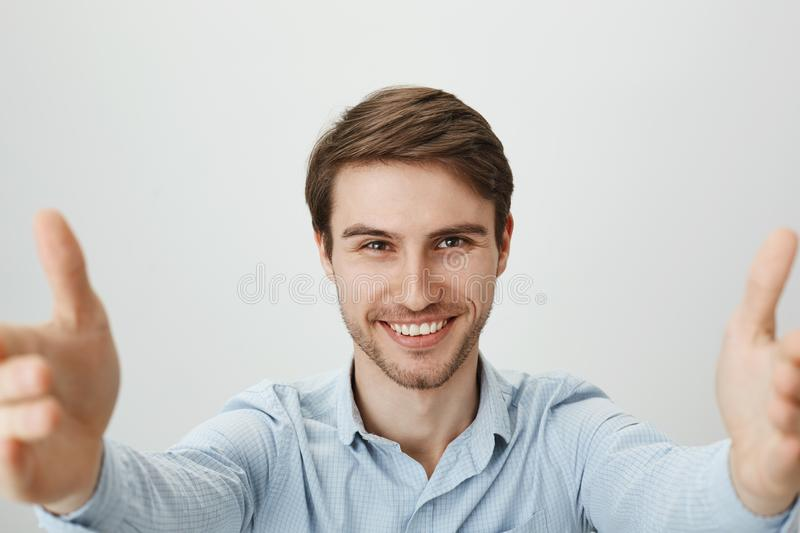 Jump and I will catch you. Upper angle shot of handsome stylish caucasian man with bristle, smiling confidently and. Pulling hands towards camera to grab stock photo
