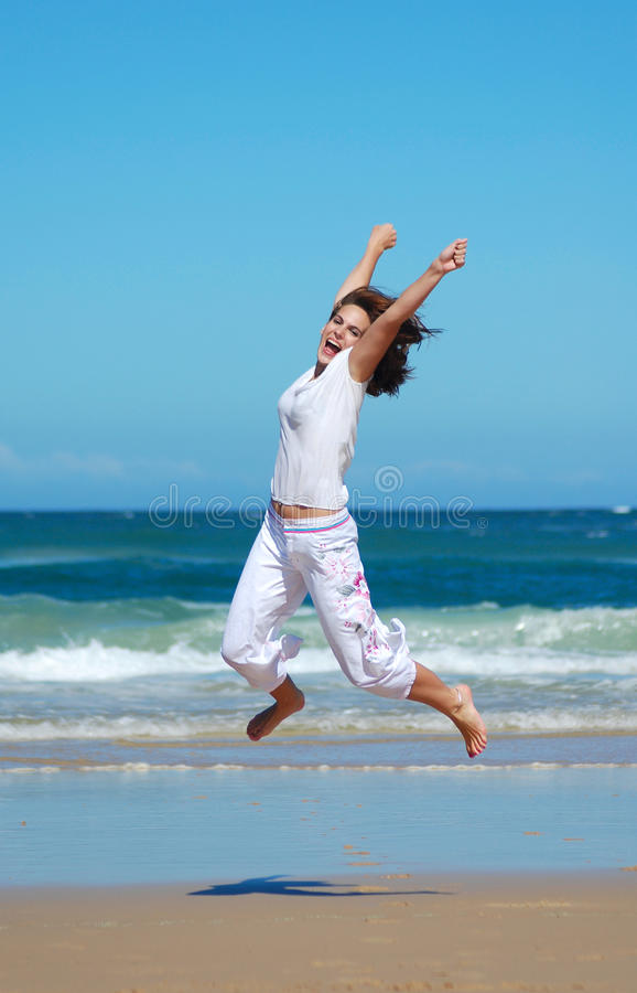 Jump for joy. A beautiful Caucasian teenage woman, dressed in white, with happy smiling facial expression jumping and raising up her arms in the blue clear sky