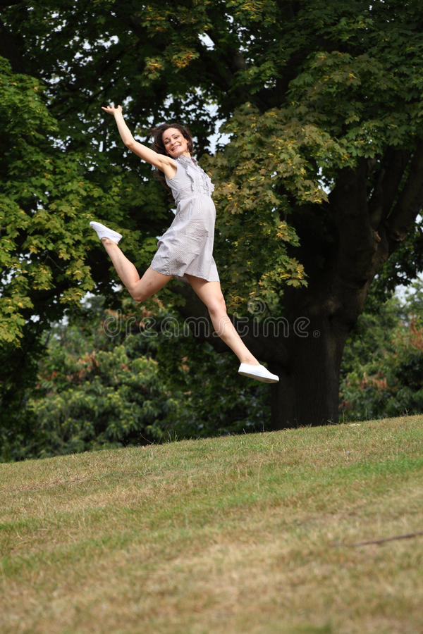 Jump for joy beautiful girl in countryside leaping stock photo