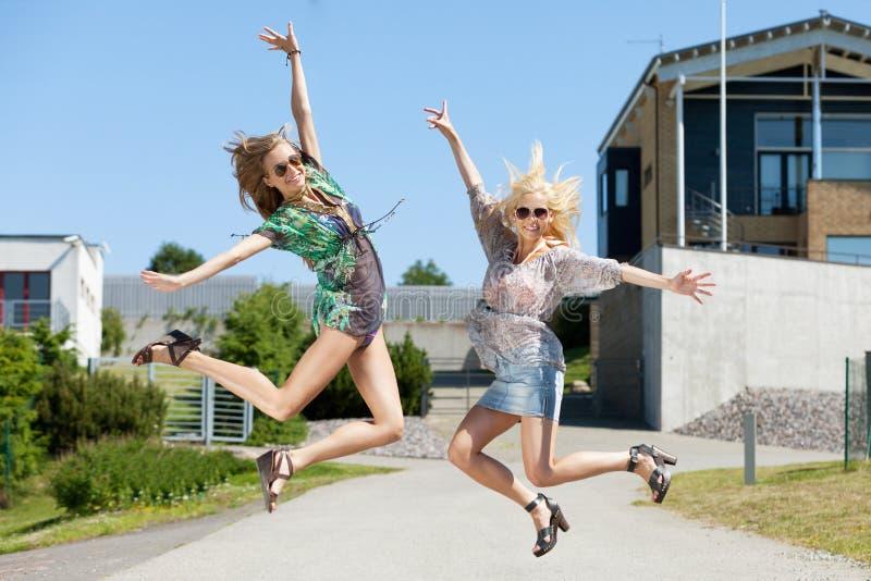 Jump of joy. Two women jumping of joy stock image