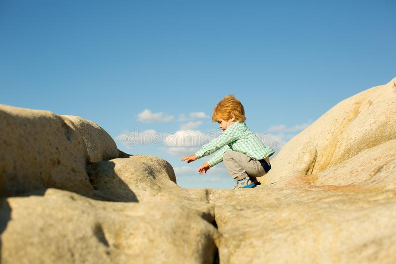 Jump. Jumpers on the rocks. Leisure. Child in nature. Greek stones near the sea. Fun. royalty free stock photography