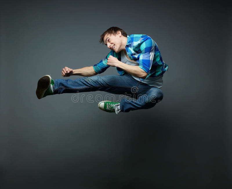 Jump and kick. Energetic guy jumping with fists clenched tight and kicking the air stock photo