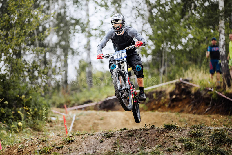 Jump over hill male extreme athlete bike. Magnitogorsk, Russia - July 23, 2016: jump over hill male extreme athlete bike during National championship downhill stock image