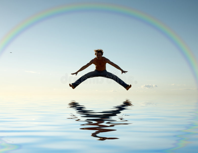 Jump over water under rainbow stock photo