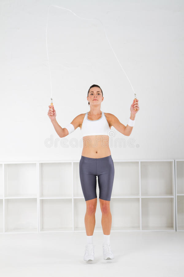 Jump rope. A pretty young fit woman using jump rope in studio stock photography