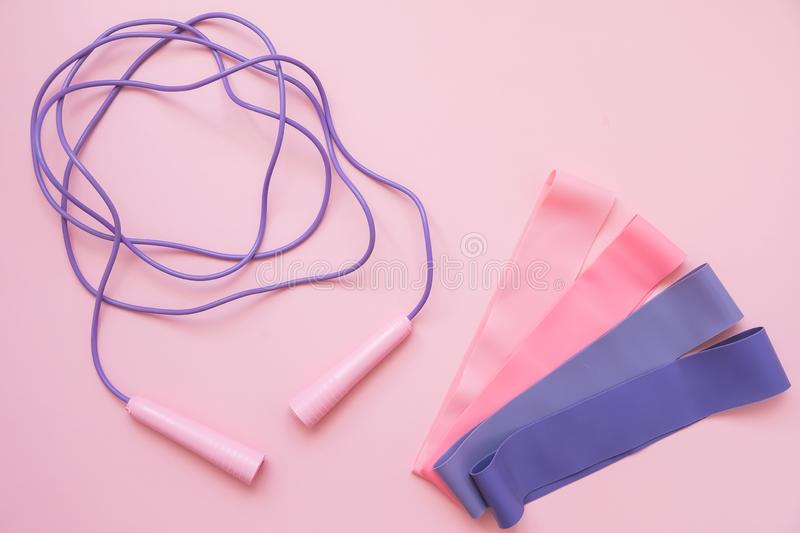 Jump or skipping rope  and fitness elastic band on pink background. Fitness trend. Sport concept. Jump or skipping rope and fitness elastic band on pink royalty free stock images