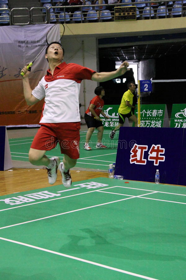 Jump smash. A Amateur badminton player jump up in the air ready for a smash royalty free stock photo