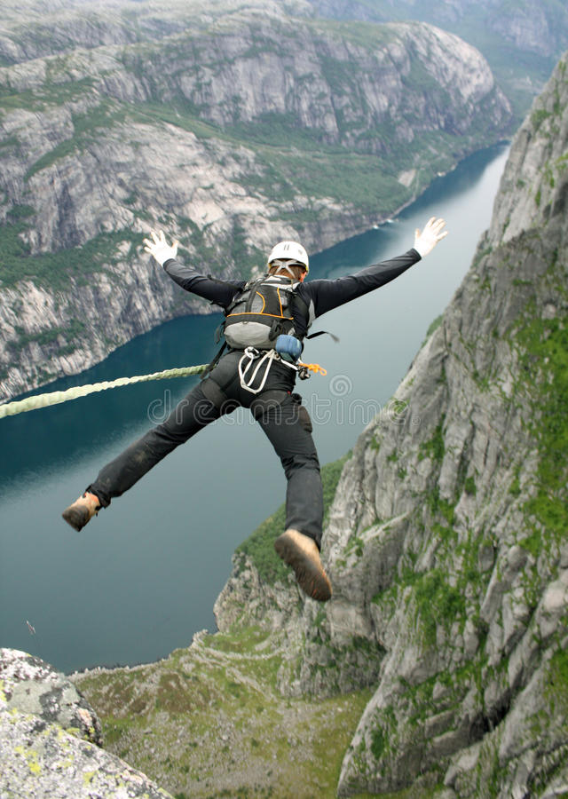 Jump to rope. BASE jump off a cliff stock photography