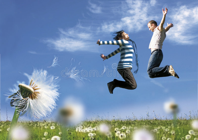 Jump together. Couple having fun in a meadow full of dandelions