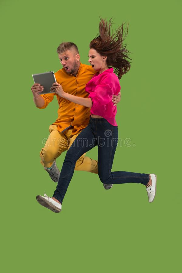 Jump of young couple over green studio background using laptop or tablet gadget while jumping. royalty free stock image