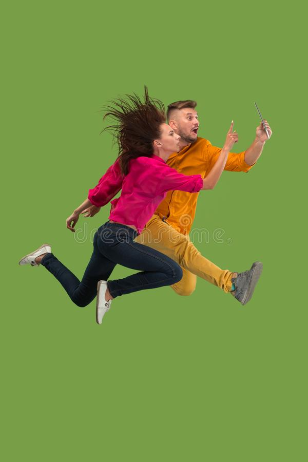 Jump of young couple over green studio background using laptop or tablet gadget while jumping. royalty free stock photos