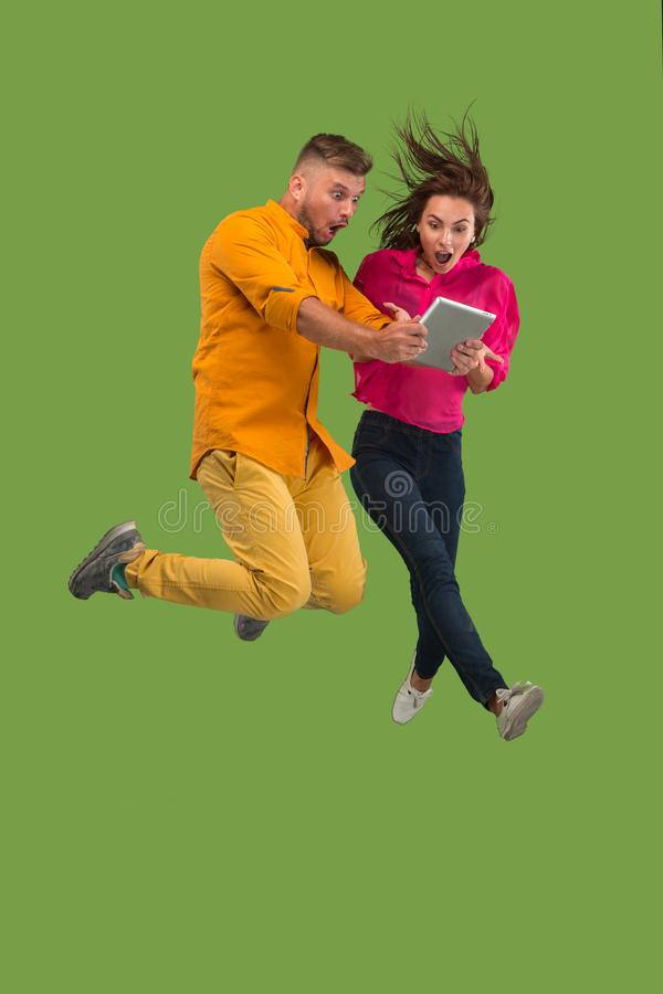 Jump of young couple over green studio background using laptop or tablet gadget while jumping. stock image
