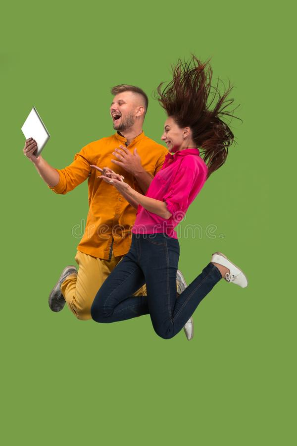 Jump of young couple over green studio background using laptop or tablet gadget while jumping. royalty free stock images