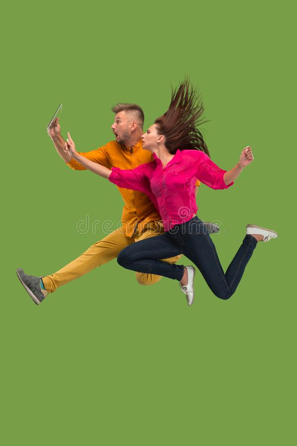 Jump of young couple over green studio background using laptop or tablet gadget while jumping. stock photos