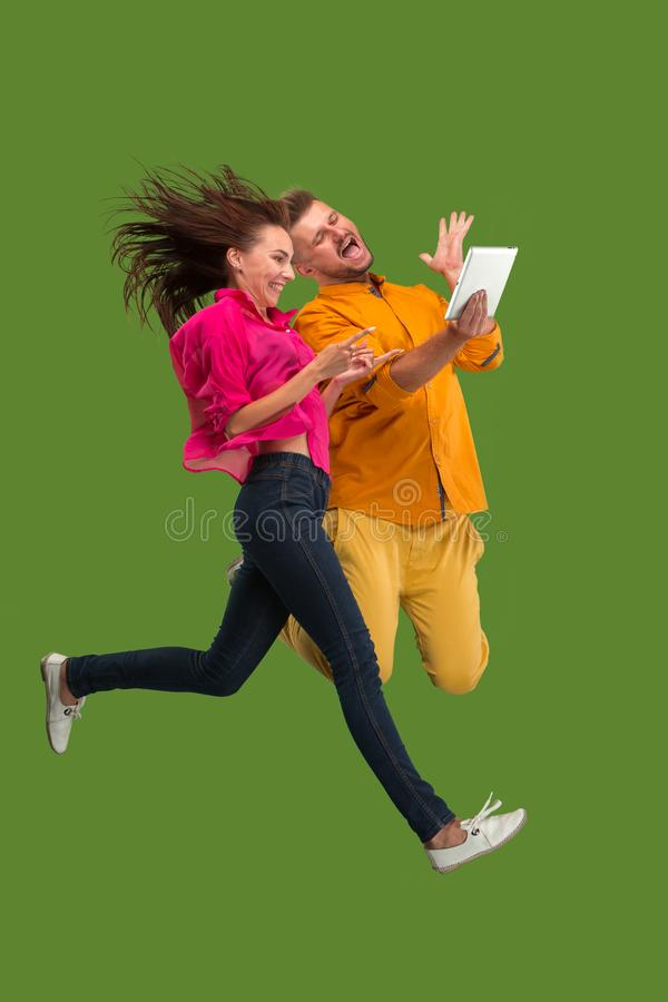 Jump of young couple over red studio background using laptop or tablet gadget while jumping. royalty free stock images
