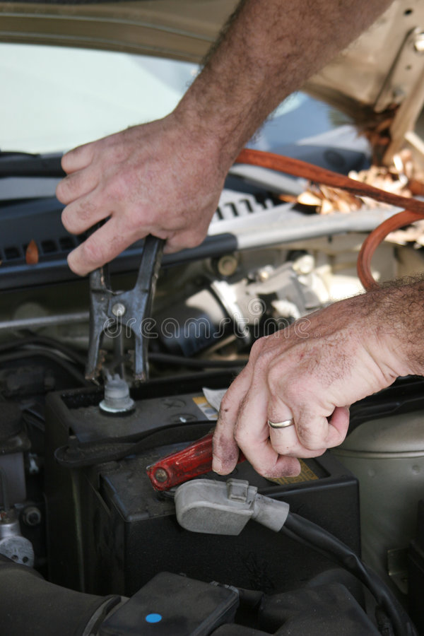 Jumper Cables. A closeup of a mechanics hands using jumper cables on a car battery royalty free stock image