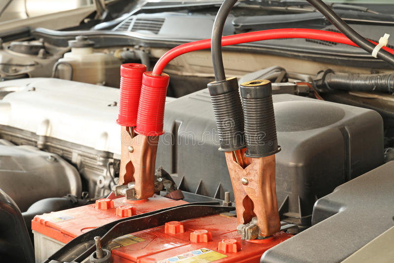 Jumper cables on a car. Jumper cables is charging battery on a car royalty free stock photos
