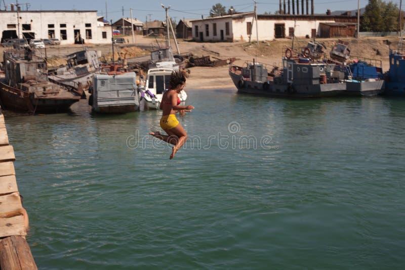 Jumpin della donna in lago fotografia stock