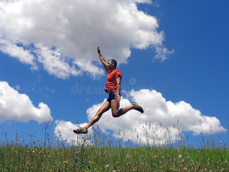 Jumping. Happy young man jumping in the air royalty free stock photography