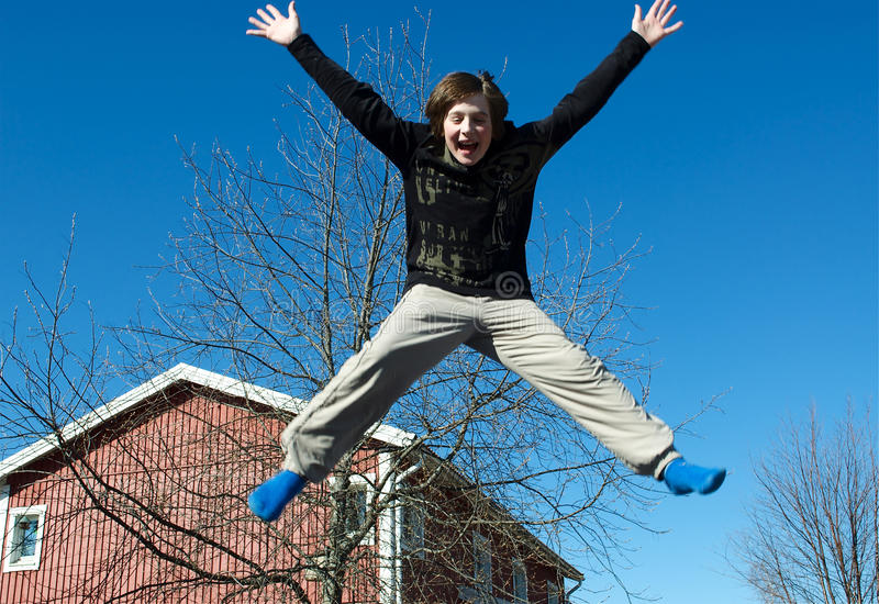 Jumping boy. Happy jumping boy on a blue sky background stock photography