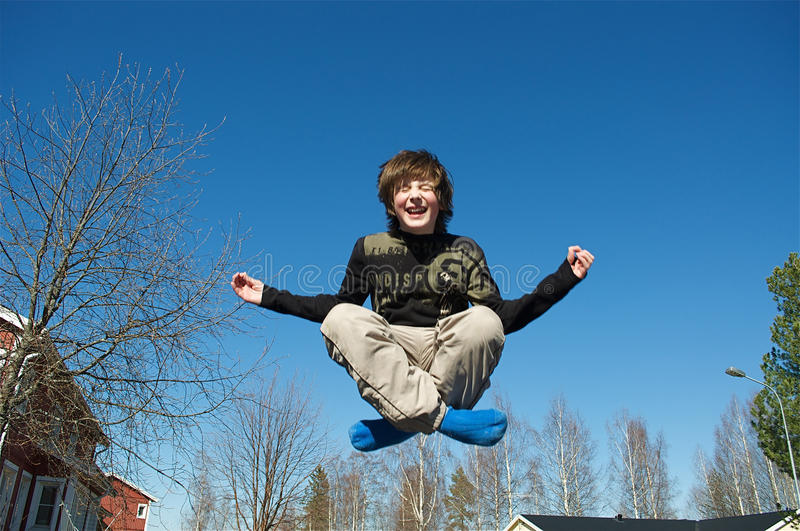 Jumping boy. Happy jumping boy on a blue sky background stock image