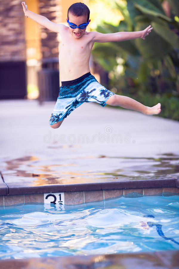 Jumping boy in the air, heading into the pool stock photos