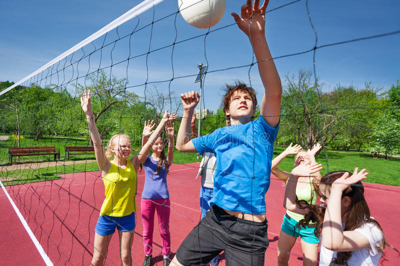 Jumping boy for ball plays volleyball with teens stock image