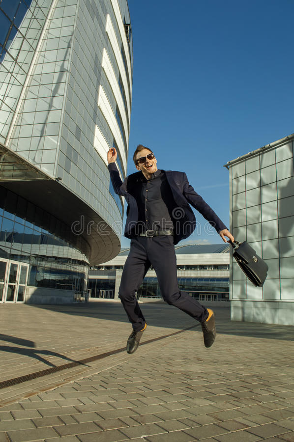 Jumping businessman with briefcase in hand royalty free stock photography