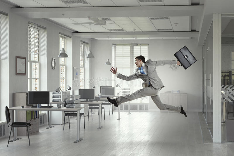 Jumping businessman in office. Mixed media . Mixed media. Young successful businessman in modern office jumping high. Mixed media stock photos