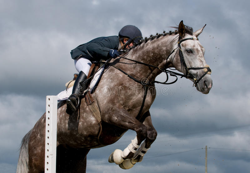 Jumping competition. Horseman at jumping competition jump an obstacle with is horse royalty free stock images