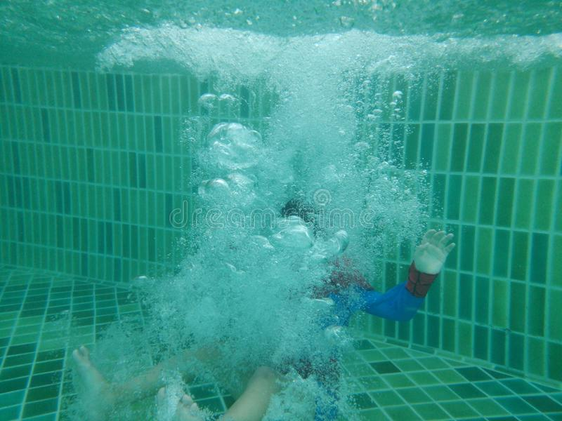 Jumping deep down underwater with splashes and foam. royalty free stock photography