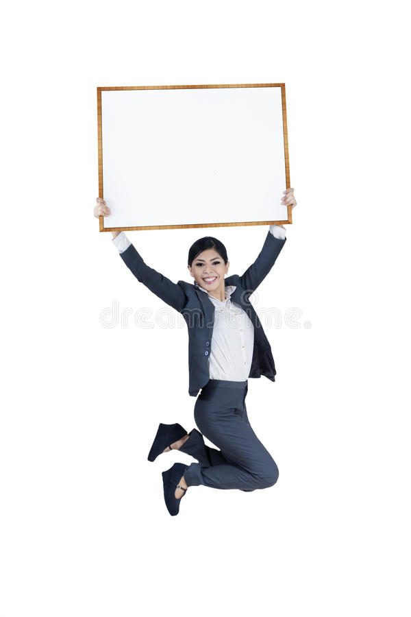 Jumping excited businesswoman holding blank board stock images