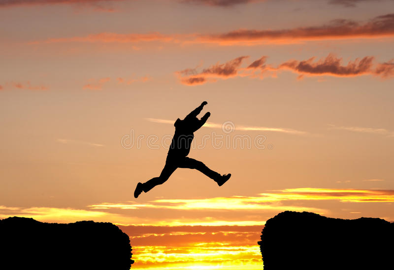 Jumping a gap in sunset. Silhouetted man jumping a gap in sunset royalty free stock photos