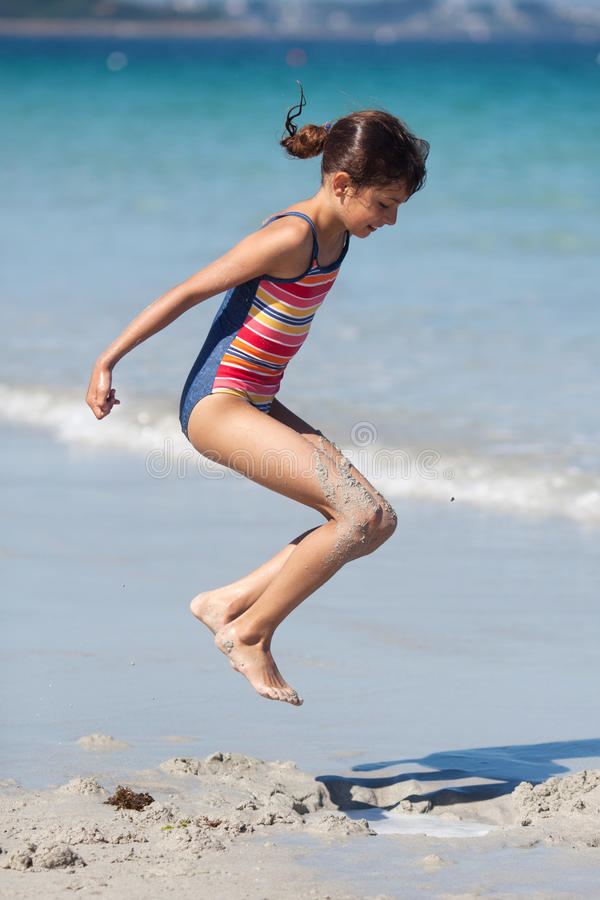 Jumping girl at the beach stock images