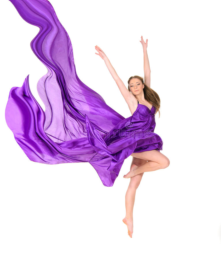 Jumping girl dancer in flying dress. Attractive jumping girl dancer in flying purple dress stock photo